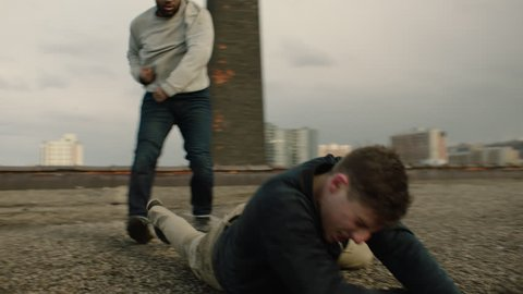 Caucasian man is knocked to the floor as he fights an African American man on a warehouse rooftop with skilled kicks and punches in overcast sunlight. Medium shot in 4K with an Alexa Mini camera