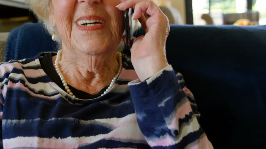 Close up of a Caucasian senior retired woman with glasses talking on mobile phone in living room at home while sitting on a sofa.
