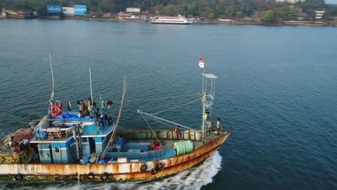 Aerial view. An old rusty fishing ship floating on the river at sunset. Flying around an Indian professional fishing boat at low altitude.