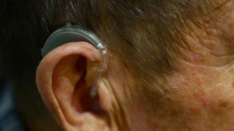 old man using hearing aids