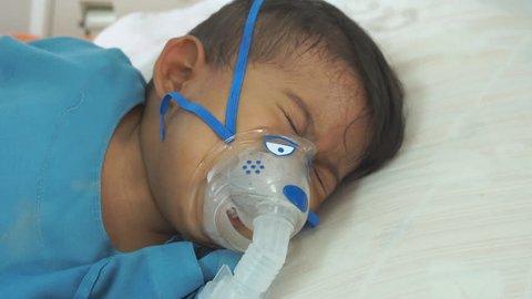 Little boy crying while use making inhalation with nebulizer