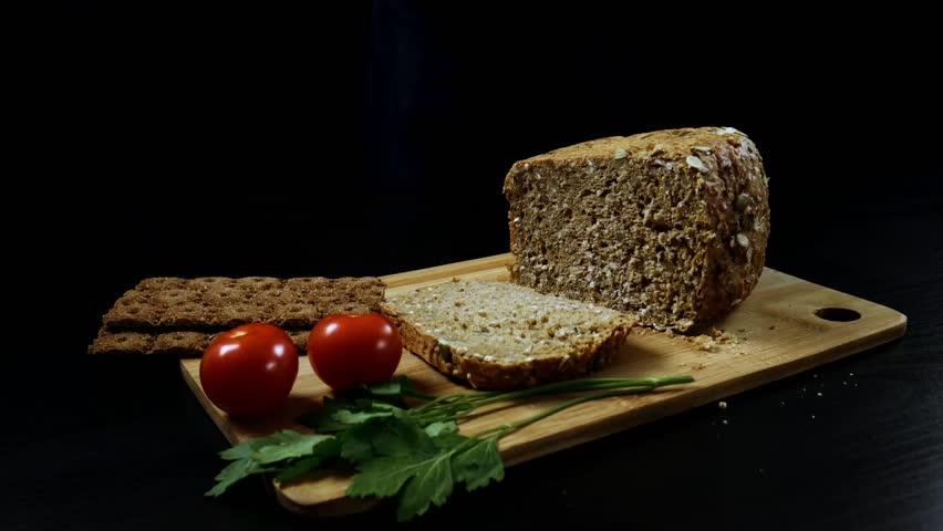 A man nervously cuts grain bread on a cutting wooden board. | Shutterstock HD Video #1020868591