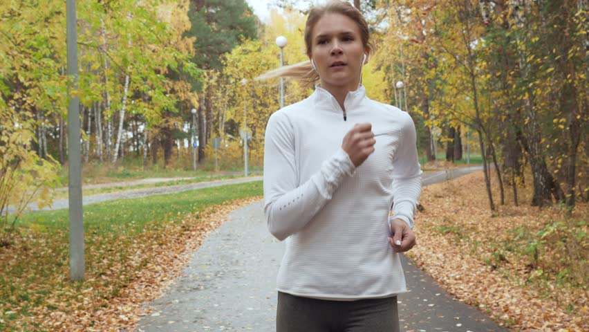 RUSSIA, TYUMEN - OCTOBER 08, 2018. Gilyevskaya roscha. Front view on young blonde woman running in the autumn park. Slow motion 60 FPS. Steadicam stabilized shot. | Shutterstock HD Video #1020873151