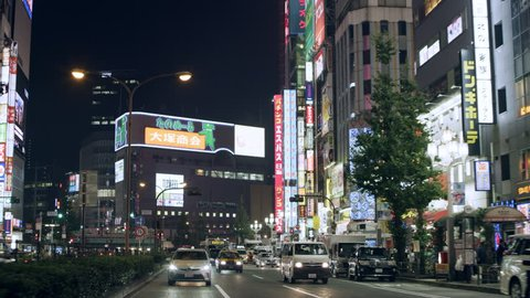TOKYO, JAPAN - CIRCA October, 2018: Cars driving in a busy street past buildings with multiple advertisements at night. Wide shot on 4k RED camera