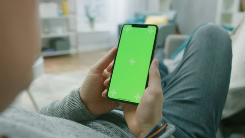 Man at Home Lying on a Couch using Smartphone with Green Mock-up Screen, Doing Swiping, Scrolling Gestures. Screen Has Tracking Markers. Over the Shoulder Camera Shot.