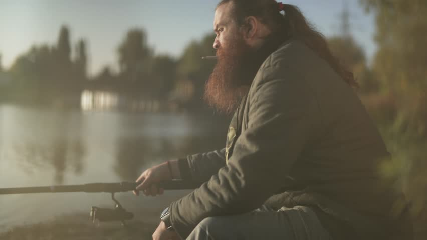 Bearded fisherman fishing on the lake. Fisher smokes sigarrette on fishing. | Shutterstock HD Video #1020996751