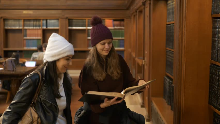 Two women doing research in a library | Shutterstock HD Video #1021004341