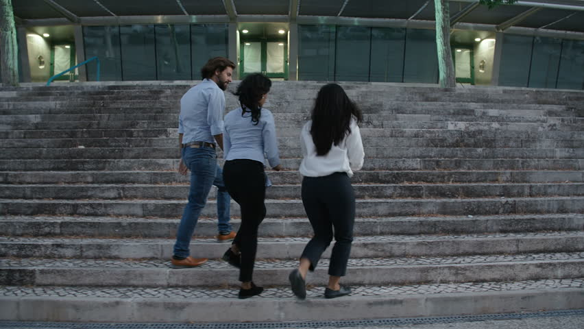 Three young business people returning from their break. One male and two females going up stairs into office building. Dolly footage. Business people concept.