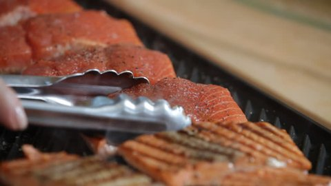 salmon fish cooking on grill as chef flips with tongs
