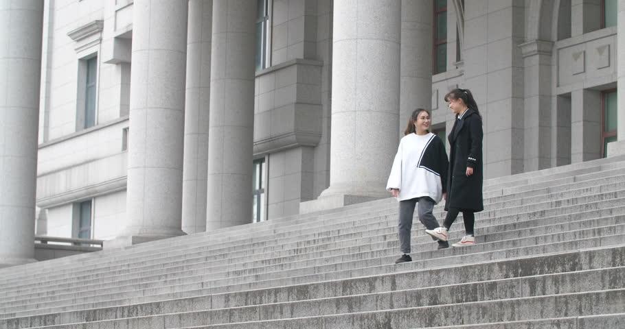 Two girl students walking up the steps hanppily together | Shutterstock HD Video #1021064851