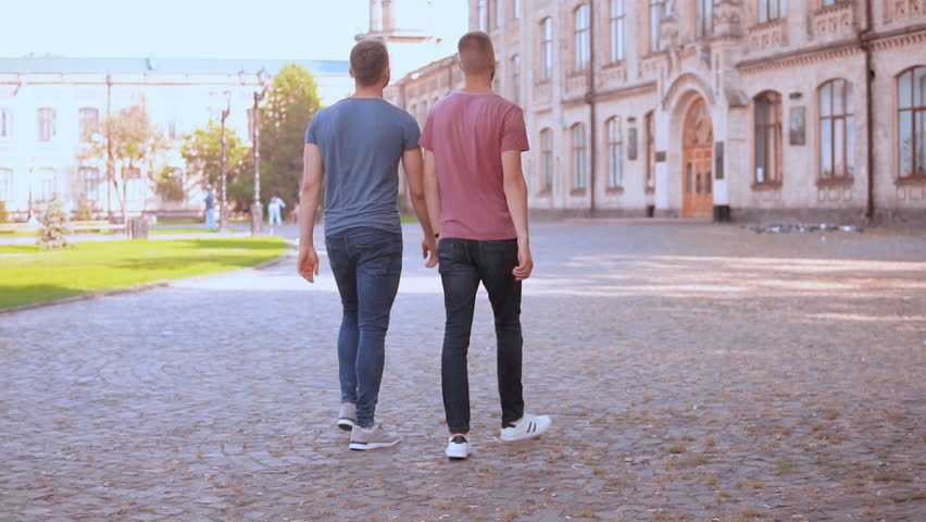 people walks in town with old architecture caucasian young men wearing casual t-shirt stroll in campus area.