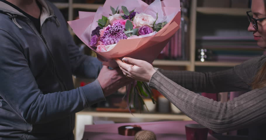 Close up of man buying bouquet of flowers and paying by cash. Florist selling beautiful flowers to a man. | Shutterstock HD Video #1021092661