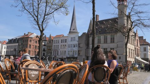 Ghent, Belgium - 10.04.2018: People sitting in caffe at the  Vrijdagmarkt square in Ghent where is the statue of  Jacob van Artevelde. Square is in the historic center of Ghent.
