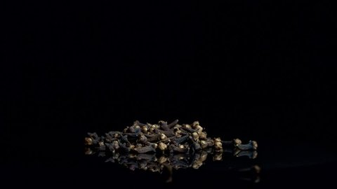 Dry cloves falling on black background in slowmotion. Spicy food ingredient.