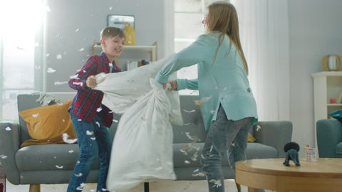 Adorable Little Boy and Sweet Little Girl Have a Pillow Fight in the Sunny Living Room. Siblings Having Fun Fighting with Pillows, Feathers Flying Around. In Slow Motion