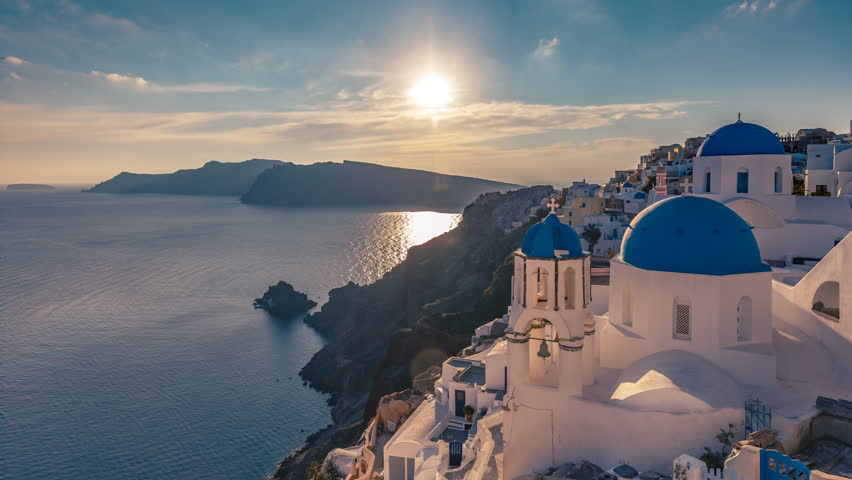 Beautiful view of Churches in Oia village, Santorini island in Greece at sunset, with dramatic sky. 4K day to night transition timelapse.