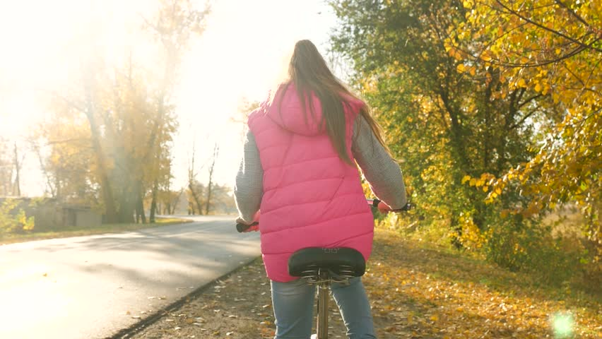 young girl riding bike on road in autumn park and smiling. Slow motion. #1021248211