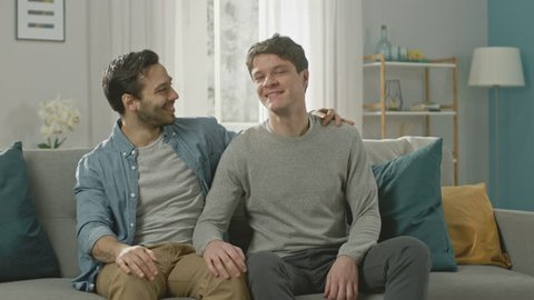 Cute Attractive Male Gay Couple Sit Together on a Sofa at Home. Boyfriend Puts His Hand on Partner's and They Hug. They are Happy and Smiling. They are Casually Dressed and Room Has Modern Interior.