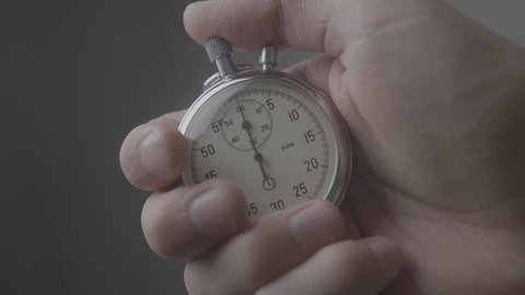 Close-up of one person starting up a stopwatch at grey background. 4K, 10 BIT, 4:2:2.