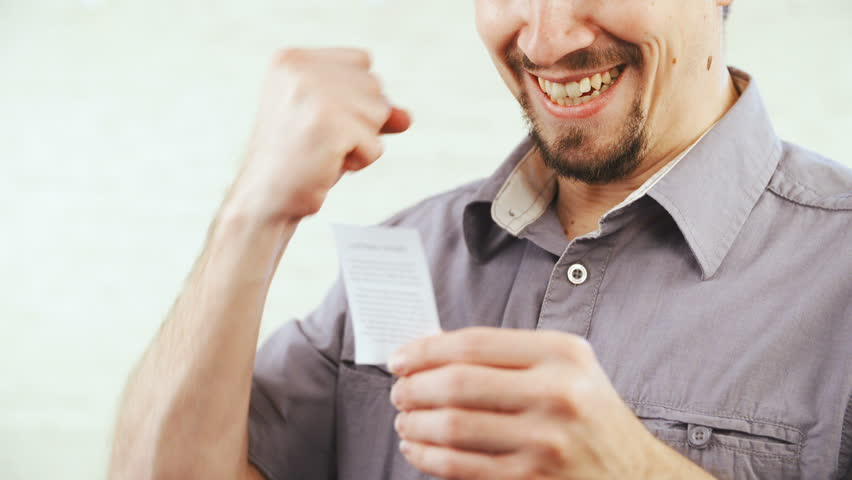 Winning the lottery/bet ticket and happy about it HD. Person mouth expression in focus after checking the lottery ticket and smiles. | Shutterstock HD Video #1021295431