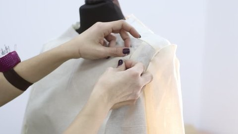 Dressmaker pins up a jacket in the initial stage of tailoring using sewing pins in a sewing workshop