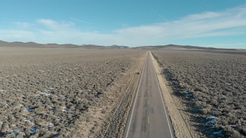 Aerial-Flying over sagebrush lined long straight desert road to vanishing point at horizon and far distant mountains