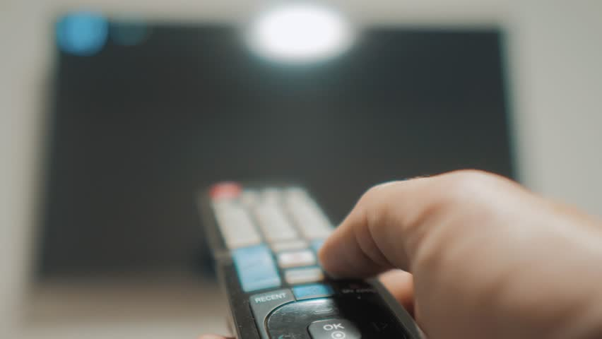 Man hand holding the TV remote control and turn off smart tv. Channel surfing. Close up mans hand holding TV remote control and changing lifestyle TV channels. blurred background | Shutterstock HD Video #1021321351