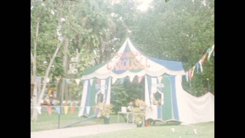 1950s: Colorful tent at fair. Flowers. Carousel and booths at fair. Two women and man walk by reflecting pond and garden. Driving down road.
