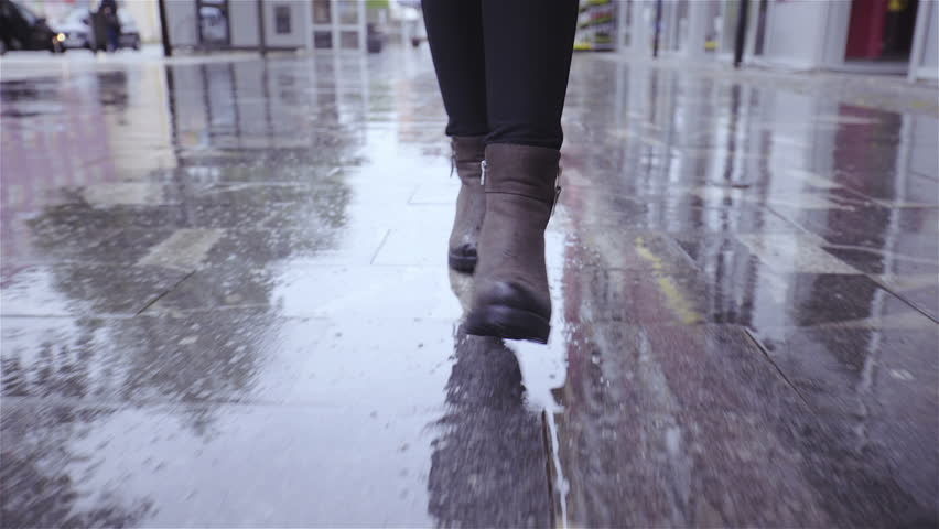 Walk in rain close up tracking HD. Low angle gimbal stabilizer shot of female boots in focus walking towards the camera on wet surface. | Shutterstock HD Video #1021379011