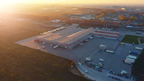 Aerial view of logistics center with warehouse, loading hub with many semi-trailers truck load/unload goods at sunset