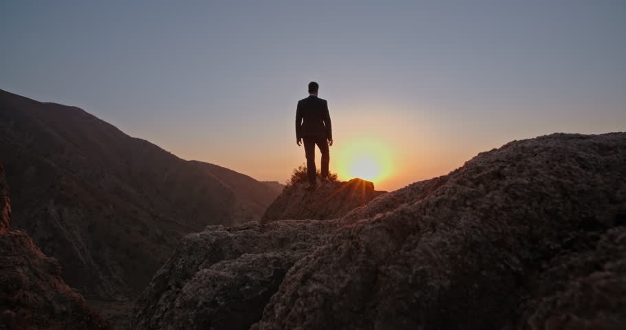 Young successful bsinessman wearing suit and tie standing on top of a mountain, raising his hands - way to success, on top of the world concept 4k | Shutterstock HD Video #1021483621