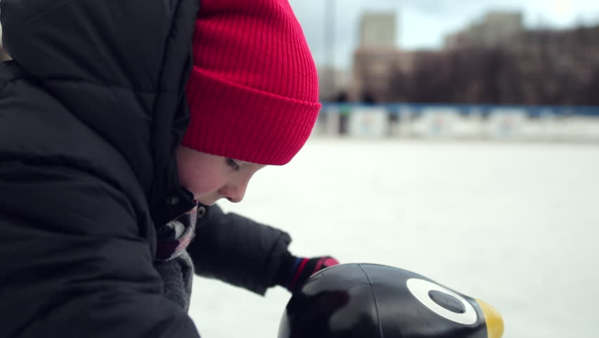 One little kid boy having fun with skates and plastic penguin. Happy children in winter clothes have fun skating on ice. Slow motion. Cold winter weather - Video | Shutterstock HD Video #1021492351