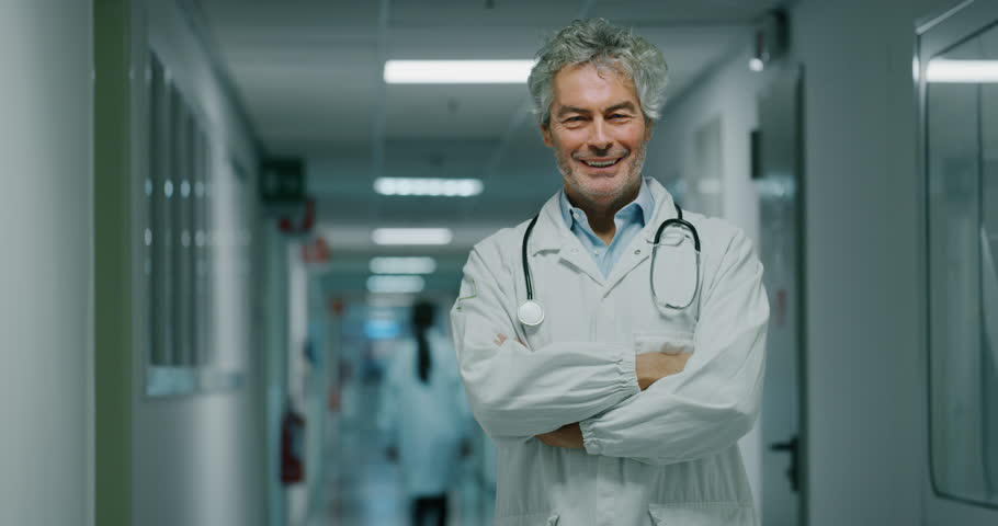 Portrait of smiling male doctor satisfied with his job in a corridor of a hospital. Concept of medicine, technology, health care and people, hospital | Shutterstock HD Video #1021499461