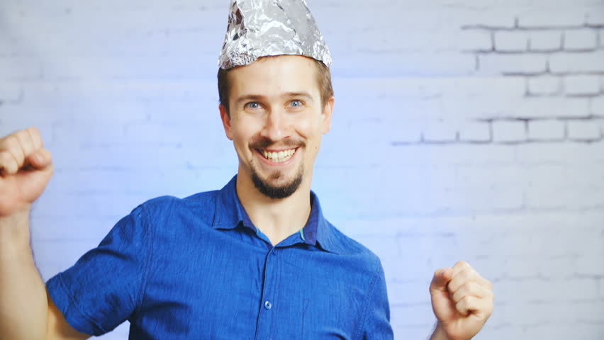47b934f4d97 The tin-foil hat person mocking the stereotypes meme HD. Static portrait  shot of a man in focus wearing a blue elegant shirt. Shoot on the bricked  wall ...