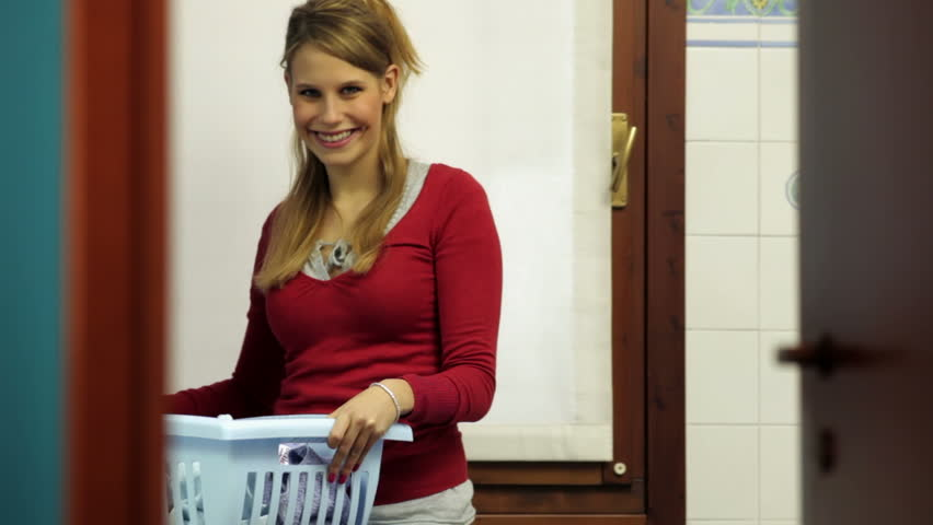 Young caucasian woman taking clothes out of washing machine and looking at camera, smiling. Girl, housewife, wife
