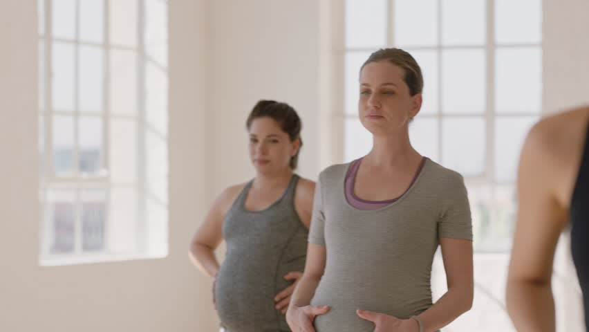 young pregnant caucasian woman in yoga class practicing warrior pose enjoying healthy lifestyle group exercising in fitness studio at sunrise #1021563571