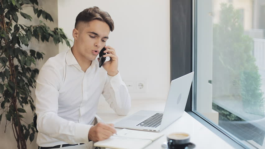 Medium shot of concentrated young businessman taking notes in notebook when talking on phone during coffee break | Shutterstock HD Video #1021573591