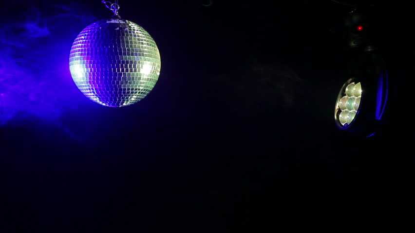 Mirror disco ball on a black background with searchlight rays iridescent in different colors in the smoke. #1021638451