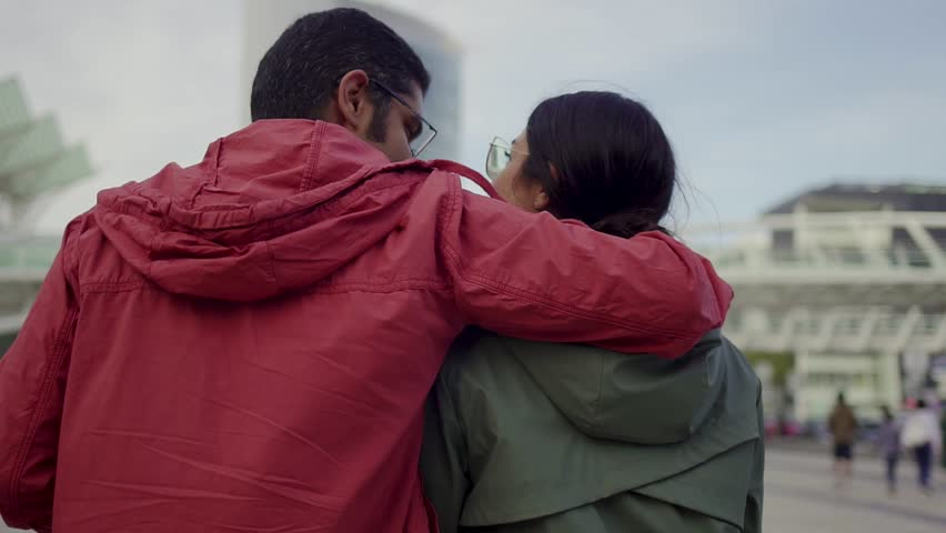 Rear view of hindu young couple strolling outdoor. Couple in love hugging and talking during walk. Relationship concept | Shutterstock HD Video #1021696621