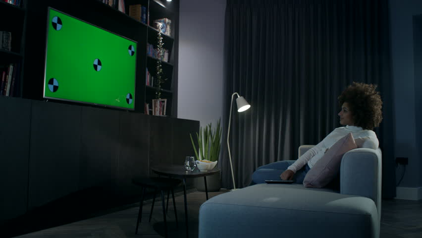 Young woman at home watching a tv on a large flat screen tv. She changes the channel using the remote control. | Shutterstock HD Video #1021744201