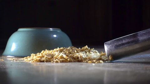 Slow motion close POV shot from ground level of the straight metal tube from a vacuum cleaner sucking up a heap of dry wheat breakfast cereal, next to an upturned bowl on the floor.