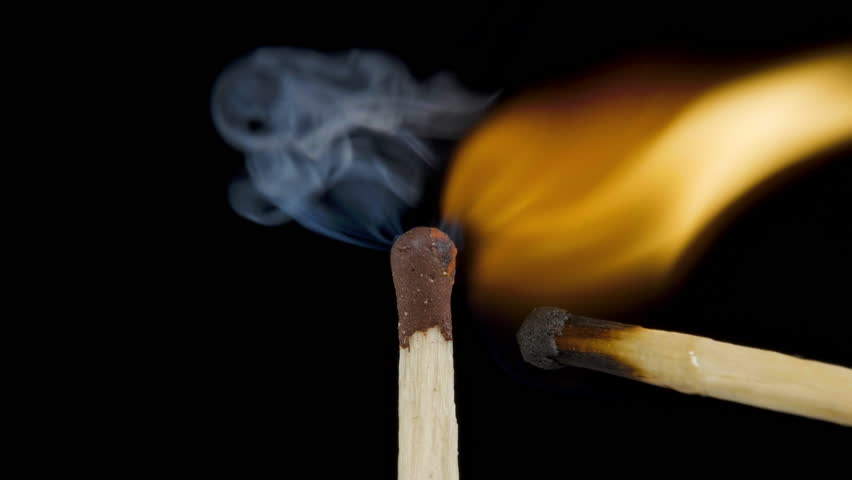 Macro fire burning on matchstick, studio shot isolated on black background
