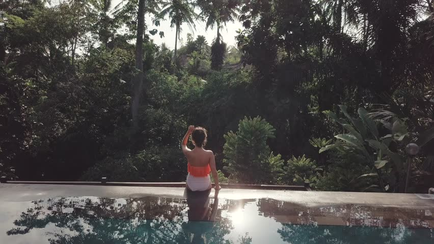 Girl sitting on the edge of the endless swimming pool with the amazing jungle view aerial footage from the back | Shutterstock HD Video #1021805701