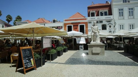 Cascais, Portugal - August 6, 2017: Monument of Portuguese poet Luis De Camoes on Largo Luis de Camoes with cafes and restaurants in Cascais center. People enjoying summer vacations.