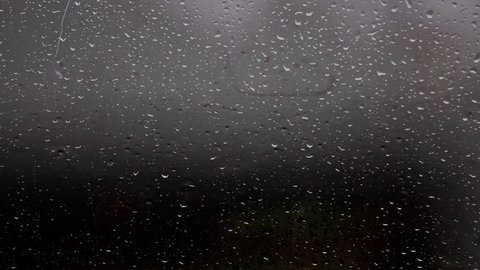 Rain falling on window surface,rain drops falling down on glass,rain on glass with sound