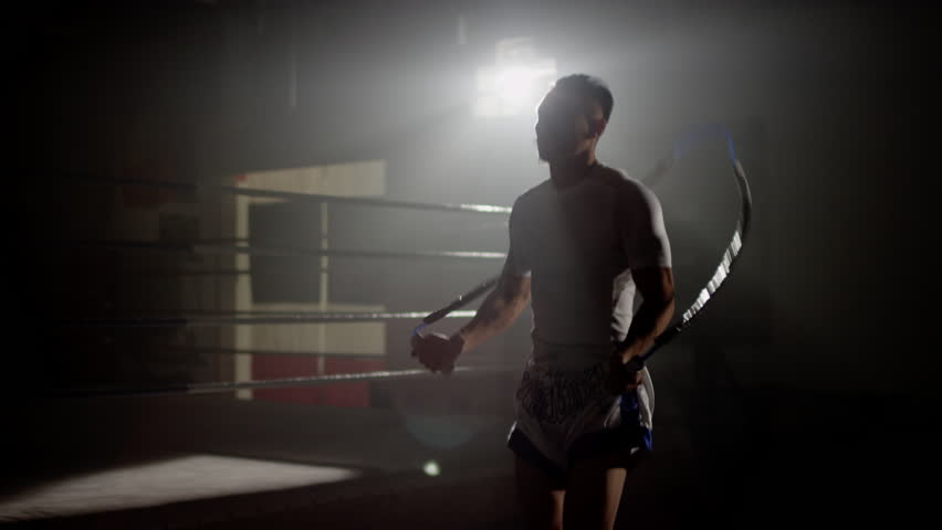 Muay Thai fighter skipping in gym beside boxing ring, training backlit with flares in the background, wide shot #1021862731