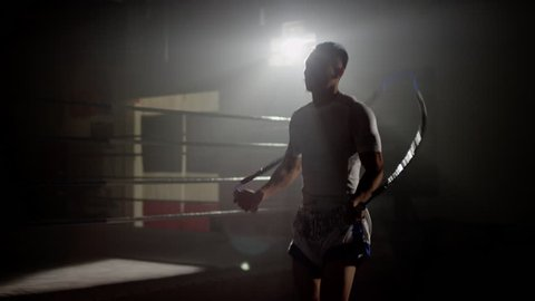 Muay Thai fighter skipping in gym beside boxing ring, training backlit with flares in the background, wide shot