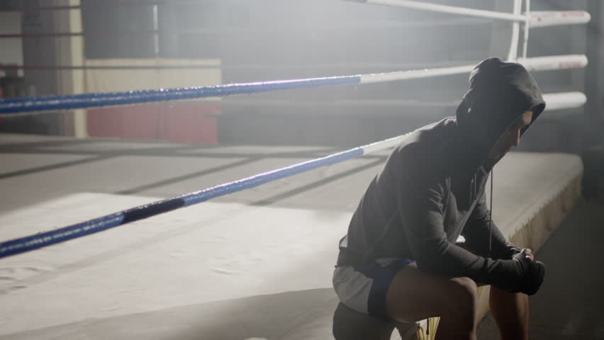 Boxer in hoodie sitting at the edge of a boxing ring deep in thought after work out in foggy gym, medium close