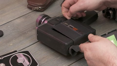 MOSCOW, RUSSIA - CIRCA OCTOBER 2018: Man using vintage 8mm home movie camera Aurora 215 Super 8 made in USSR by Lomo. Loading film cartridge. Old Soviet Russian film camera made since 1978.