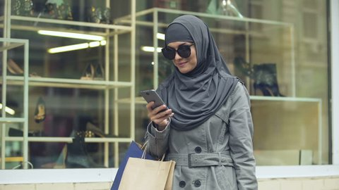Cheerful smiling woman in hijab, chatting on phone near show-window, shopping